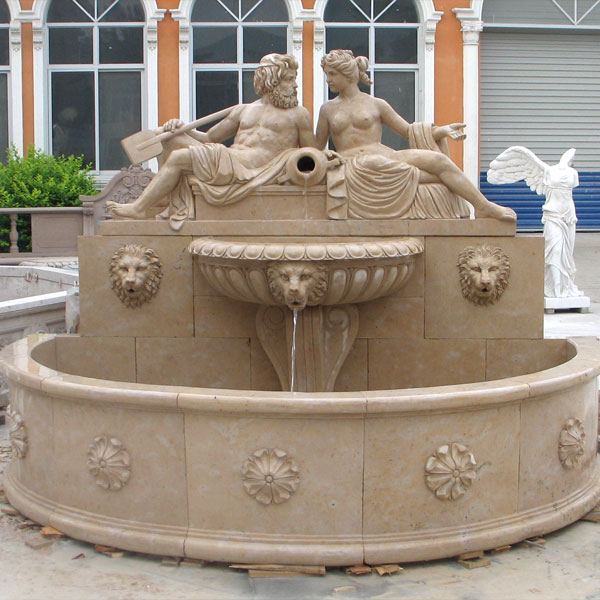 Lion head wall fountain with nude man and woman statues outdoor