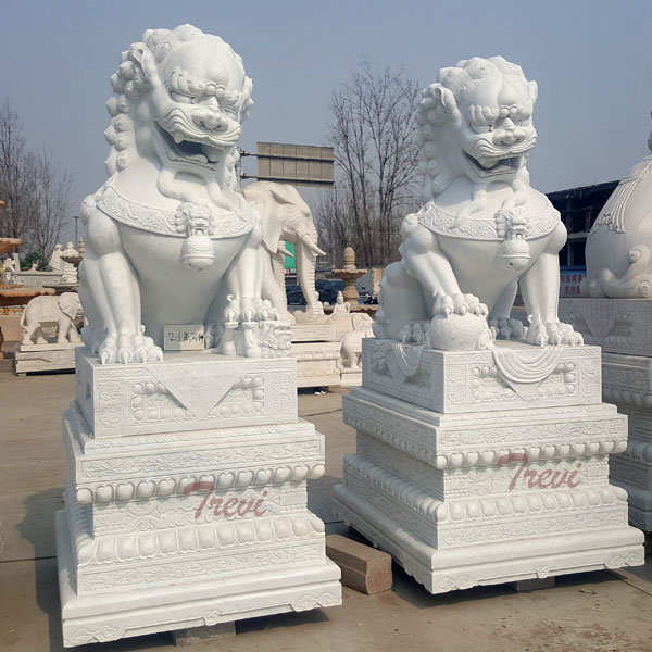 Carved stone lion guardians fu dog pair with base in front of house
